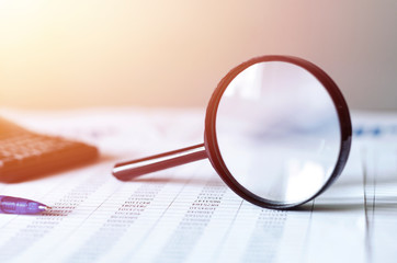 Single Magnifying Glass with Black Handle, Leaning on the financial data. Business and Finance concept,