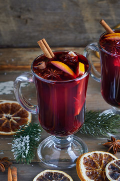 Christmas mulled wine in two glasses with fruits and spices on wooden background