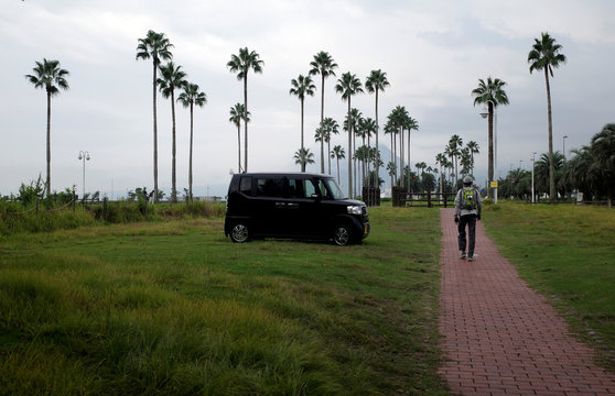 A Japanese kei-car is pictured among palm trees in Beppu