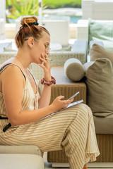 Jolie jeune femme fumant une cigarette sur un patio et téléphonant à un client sur son smartphone