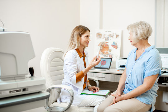 Senior woman patient talking with female ophthalmologist during a medical consultation at the ophthalmologic office. Doctor offering eye medcine for a patient