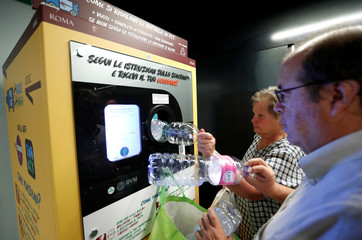 People put plastic bottles into a recycling machine in San Giovanni metro station in Rome