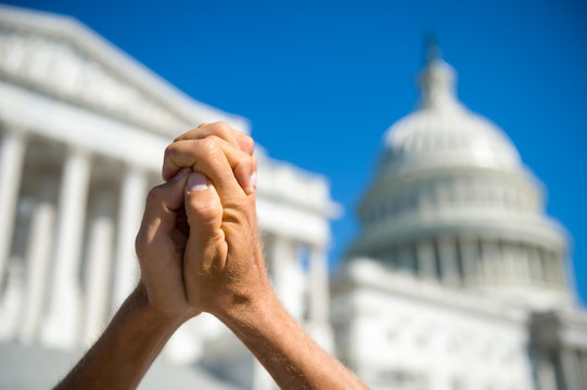 Hopeful hands clasped together in prayer in front of a bright view of the Capitol Building in Washington DC, USA