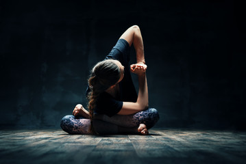 Young woman doing yoga Padmasana pose variation on dark room