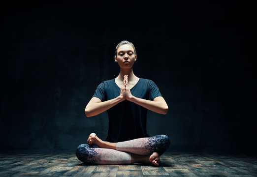 Young sporty woman practicing yoga sitting in lotus pose with namaste in dark room