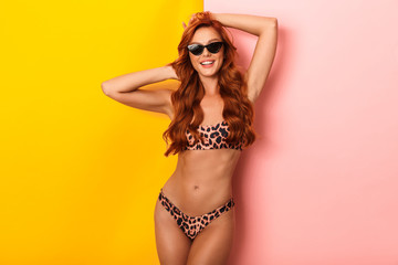 Photo of glamorous woman wearing leopard bikini and sunglasses looking at camera while smiling