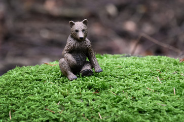 Bear toy in the forest stock  images. Sitting bear in the forest. Brown bear toy. Figurine of a bear in the forest. Bear figurine sitting on moss