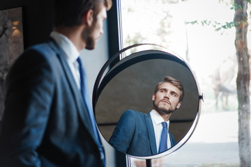 Reflection of handsome young man in full suit standing near the window in front of the mirror indoors