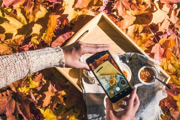 Woman is taking a picture on a smartphone of morning breakfast on a wooden tray in the autumn park with colorful maple leaves. Aerial view