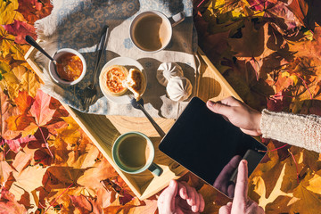 Couple of young people are looking on a tablet having morning breakfast on a wooden tray in the autumn park with colorful maple leaves. Aerial view