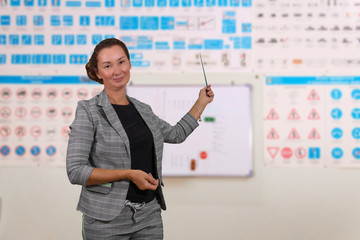woman traffic rules instructor on blurred background of the training room with traffic signs