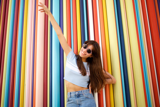 cheerful young woman laughing against colourful wall with sunglasses