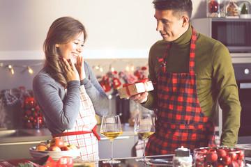 Netter Mann, der seine Freundin mit Weihnachtsgeschenk in der Küche überrascht