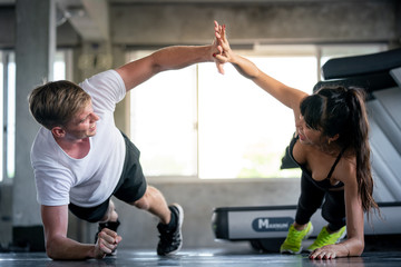 Keuken foto achterwand Fitness Young adult caucasian couple athlete man and woman in sportswear doing body balance plank exercise workout fitness touching hand together during training class in gym sport club for strong healthy.