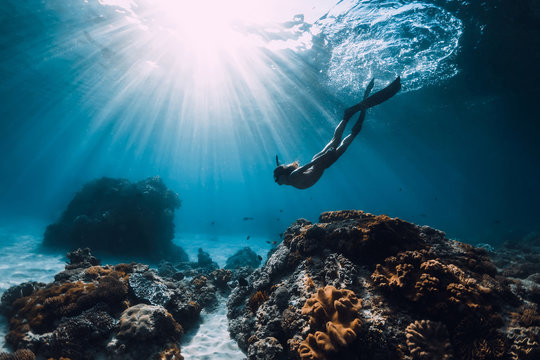 Woman freediver with fins underwater. Freediving and beautiful light in ocean