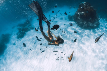 Freediver girl with fins glides over sandy bottom with fishes in transparent sea
