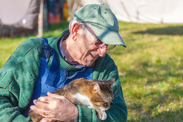 Closeup of elderly man holding his cat in his arms. Concept: friendship, love, love of animals