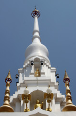 The top of a white stupa at a temple housing sacred gold relics associated with the Buddha against a blue sky background
