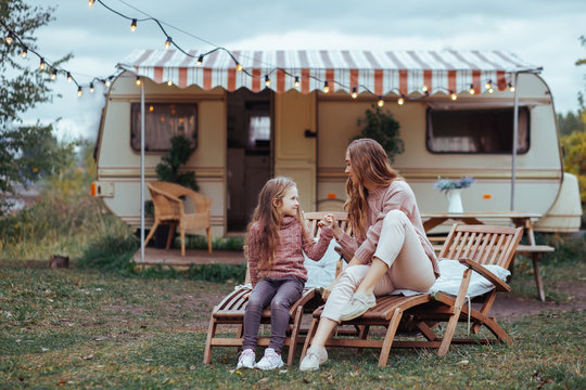 Happy family - mother and little daughter kissing and having fun in countryside on camper van vacation