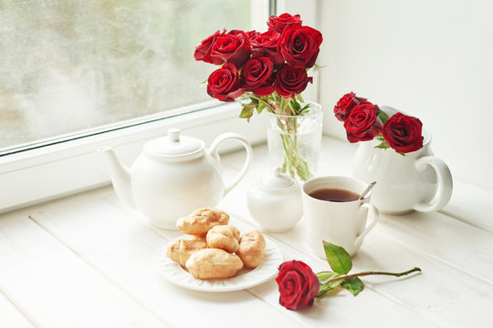 red roses, tea and croissants on a table near the window, romantic breakfast for Valentine's Day