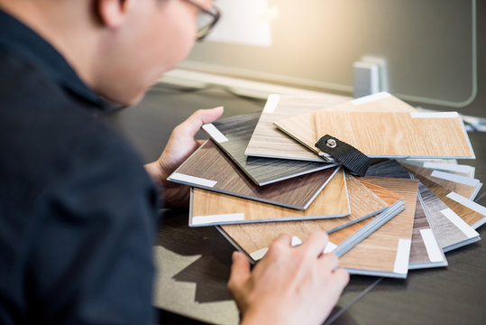Male architect or interior designer holding wooden color swatch choosing wood material for housing project. Sample of wood laminated chipboard for furniture design. Architecture and construction.