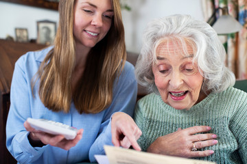 Woman Helping Senior Neighbor With Bills And Paperwork