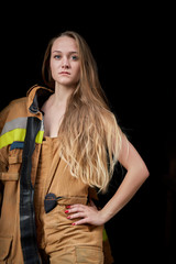 Picture of young firefighter woman in overalls on black empty background.