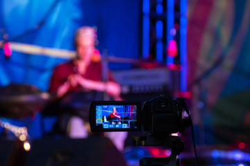 Video camera recording ethnic open air concert. Man with tank drum or hang on blurry abstract bokeh background