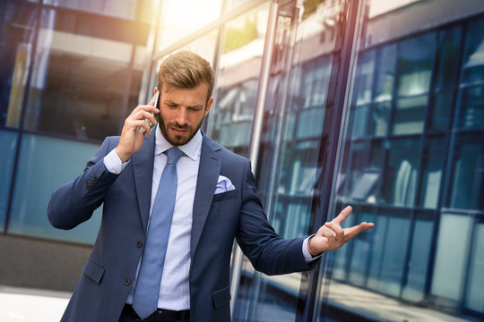 Furious businessman talking to someone over smart phone