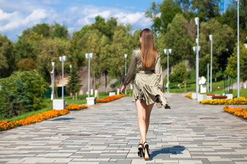 Young beautiful woman in green dress walking on the summer street