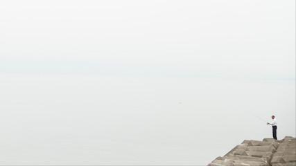 A man is seen fishing of the coast of Tanoura beach, Beppu