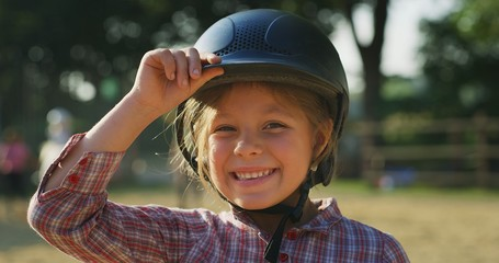 Authentic shot of a little girl with a  helmet smiling in the camera at riding stable on a sunny...