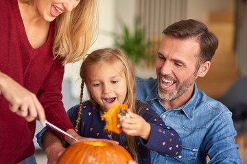Parents helping child in carving pumpkins