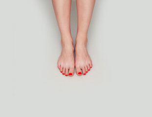 Beautiful female feet on a light gray background. Pedicure, foot