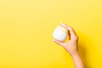 Female hand holding cream bottle of lotion isolated. Girl give jar cosmetic products on yellow background