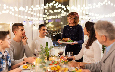 celebration, holidays and people concept - happy family having roast chicken for dinner party at home