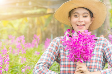 A woman gardener wearing a plaid shirt wearing a hat is holding a pink orchid in his hand. And was smiling happily. In the orchid garden Wall mural