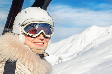 Portrait of young adult beautiful happy caucasian woman smiling on ski-lift at alpine winter skiing resort. Girl in fashion ski suit, goggles and white helmet. Winter sport vacation and tourism