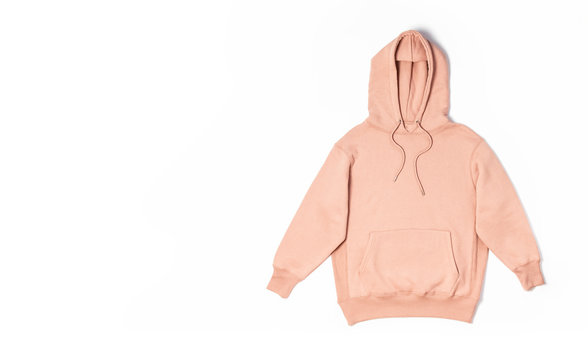 Female peach pink sweatshirt with pocket and hood isolated on white background. Fashionable women's clothing, hoody, casual youth style, sports. Autumn fashion