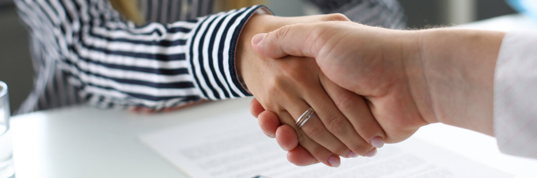 Man and woman shaking hands after productive deliberations closeup
