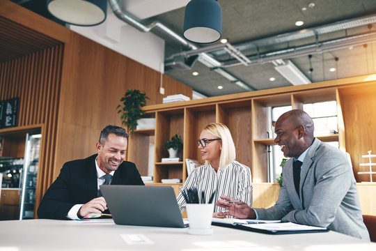Three diverse businesspeople laughing while working together in