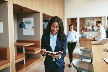 Smiling African American businesswoman walking through an office