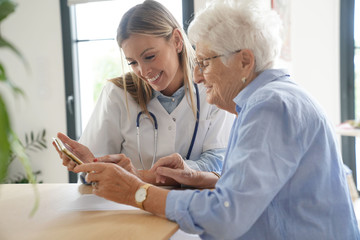 Elderly woman with nurse at home looking at tablet