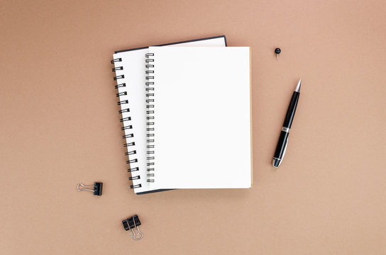 Top view brown desk above of open empty spiral notebook mockup with black stationary and pen. Copy space
