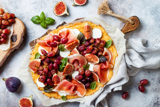 Cauliflower pizza crust with figs, proscuitto, goat's cheese and red grapes. Grain free, low carb, gluten free, keto diet concept