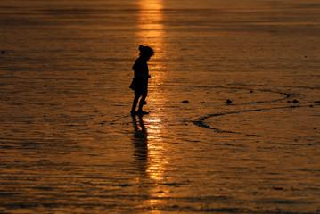 A girl walks during sunset  along the Clifton beach Karachi,