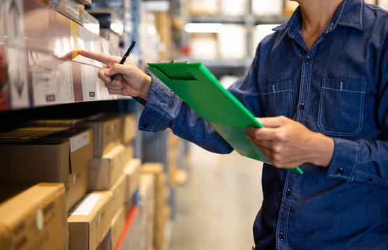 Manager man worker doing stocktaking of product management in cardboard box on shelves in warehouse. Physical inventory count.. Male professional assistant checking stock in factory.