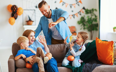 happy  family mother father and children prepare for Halloween decorate  home with pumpkins and  laughing, play and scare  with spiders.