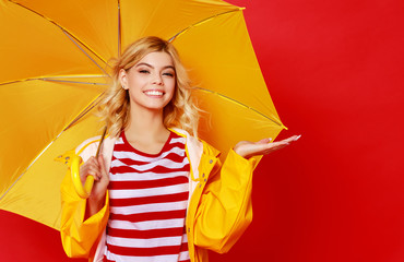 Obraz young happy emotional cheerful girl laughing and jumping with yellow umbrella   on colored red background. - fototapety do salonu