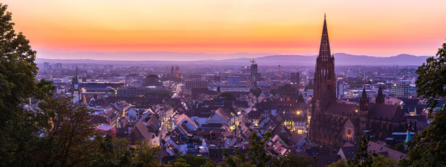 Germany, XXL panorama of skyline of freiburg im breisgau by night after sunset with red sky in magical twilight from above
